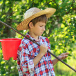 Boy wearing straw hat holding something in arm — Stock Photo