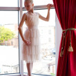 Attractive young ballerina near a window — Stock Photo