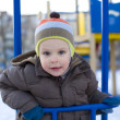 Stock Photo: Amusing kid who plays at playground in winte