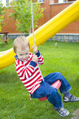 Four-year-old child riding a swing — Stok fotoğraf