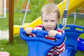 Portrait of the four-year-old kid on a swing — Stock Photo