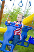 Four-year-old child riding a swing — Foto Stock