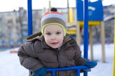 Amusing kid who plays at a playground in the winte — Stock Photo