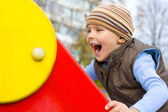 Active four-year-old boy playing at a playground — ストック写真