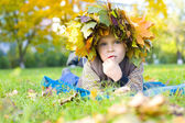 Portrait of beautiful child in wreath from autumn leaves — Stockfoto