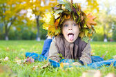 Portrait of cheerful child in a wreath from autumn leaves — Stock Photo