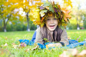 Portrait of the cheerful child in a wreath from autumn leaves — Stock Photo