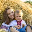 Stock Photo: Sister with younger brother on hay