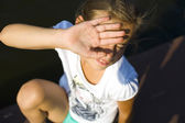 Teenage girl blinks from the sun — Stock Photo
