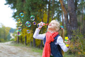 Five-year-old girl inflates soap bubbles — Stok fotoğraf