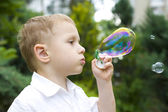 Four-year-old child plays with soap bubbles — Stok fotoğraf