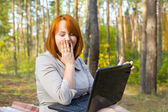 Emotional red-haired girl with the laptop — Stock Photo