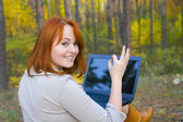 Attractive red-haired girl with laptop in the wood — Foto Stock
