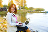 Attractive girl with laptop about a reservoir in the fall — 图库照片
