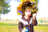 Little amusing girl in a wreath from autumn leaves — Stock Photo