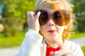 Ridiculous little girl puts on big sunglasses — Stock Photo