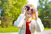 Portrait of a little girl playing in big sunglasses outdoors — Stock Photo