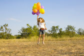 Funny little girl with balloons, bouncing — Foto Stock