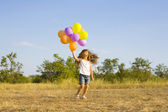 Funny little girl with balloons, bouncing — Zdjęcie stockowe