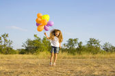 Funny little girl with balloons, bouncing — Stock Photo