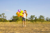 Funny little girl with balloons, bouncing — Stok fotoğraf