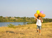Four-year girl running with balloons — Stock fotografie