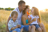 Happy young family with two children — Stockfoto