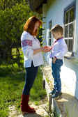 Mother with te son in Ukrainian national clothes play near the h — Стоковое фото