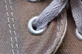 Eyelet tab of canvas shoe, with shoelace, close-up — Stock Photo