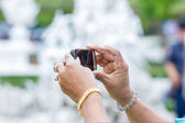 Rich woman hands taking a picture at a temple in Thailand — Stock Photo