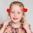 Strawberry blonde preschool girl holds two red hearts near her ears. — Stock Photo #41986987