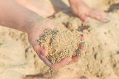 Child's hand palm with sea sand — Stock Photo