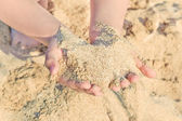 Child's hands palm with sea sand — Stock Photo