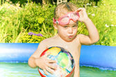 Little girl in the swimming pool taking off her swimming glasses — Stock Photo