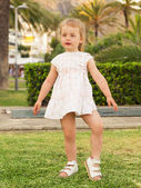 Little girl dancing on the lawn against park background — Photo