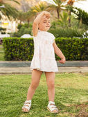 Little girl dancing on the lawn with closed eyes against park ba — 图库照片
