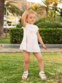 Holčička tančí na trávníku se zavřenýma očima proti parku ba — Stock fotografie