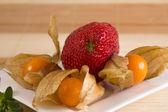 Three gooseberries and one strawberry — Stock Photo