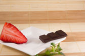 One chocolate bar and one strawberry — Stock Photo