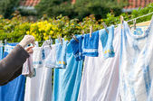 Old woman hanging laundry outdoor — Stock Photo