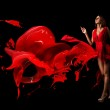 Lady in red. Red dress. Beautiful woman covered in red on a dark background. — Stock Photo
