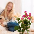 Bouquet of flowers in a room in the interior. Happy young woman sitting on sofa holding a mug at home in the living room. — Stock Photo