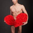 A handsome young man with a broken heart. Male man holds in his hands a red heart. Sexy man guarding a symbol of love. Broken heart lover. — Stock Photo #41663451