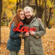 Постер, плакат: Love story Autumn Park Man and woman in a city park tells the story of his love Happy people Yellow and bright red leaves around a loving couple