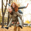 Love story. Autumn Park. Man and woman in a city park tells the story of his love. Happy people having fun. Woman on top of a man on his back. — Stock Photo #41663581