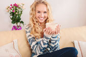 Retrato de uma mulher bonita na sala. mulher jovem feliz sentado no sofá, segurando uma caneca em casa na sala de estar. — Fotografia Stock