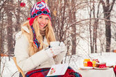 Portrait of a beautiful woman is drinking tea or coffee in the fresh air in the winter. — Stockfoto