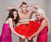 Two sexy girl holding a red heart as a symbol of love. Two woman fight over erotic character and love. Love red heart in the hands of two young attractive women blonde and brunette. — Foto Stock