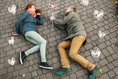 Love story. Autumn Park. Man and woman in a city park tells the story of his love. Painted flowers on the ground around a loving couple . Man gives his woman painted flower. — Foto de Stock