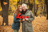 Love story. Autumn Park. Man and woman in a city park tells the story of his love. Happy people. Yellow and bright red leaves around a loving couple. — Foto Stock